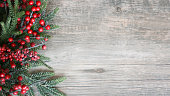 Holiday Evergreen Branches and Berries Over Rustic Wood Background