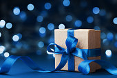 Holiday gift box or present with bow ribbon against blue bokeh background. Magic christmas greeting card. Copy space for data or design.