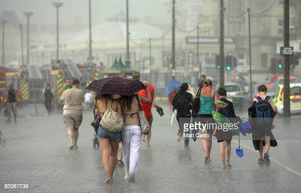 Holiday makers are caught in a sudden rain storm on the beach close to the Grand Pier on July 28 2008 in WestonSuperMare England A major fire has...