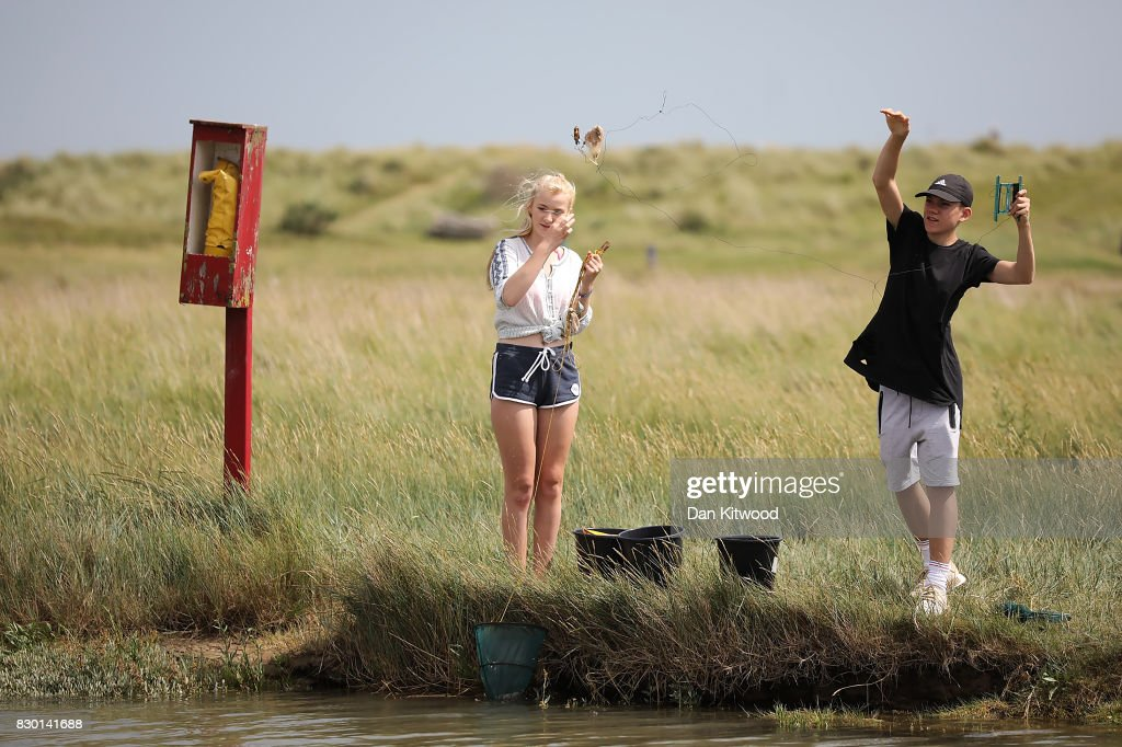 Holiday makers fish for crabs from the bank of a creek on August 11, 2017 in Walberswick, England. Much of the country is expected to enjoy a sunny spell over the weekend after a period of unseasonably wet weather.