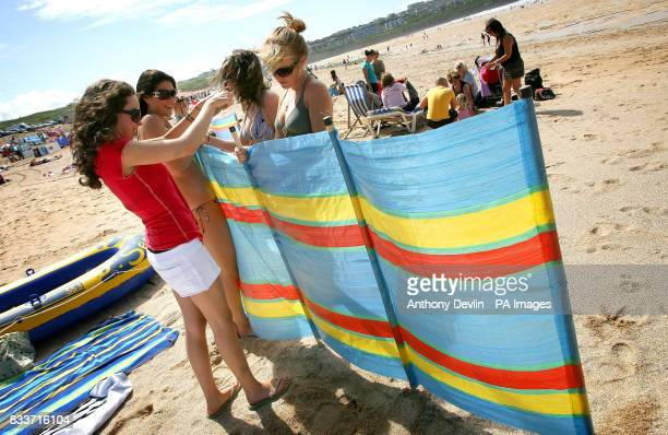Sophie Morris Charlotte Lewis Ellie Houghton and Ester JacksonTaylor put up a windbreaker on Fistral Beach in Newquay as warm weather returns