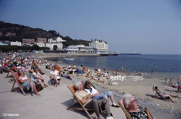Holiday makers soak up the sun relaxing in deckchairs on the coast of seaside resort Llandudno between Bangor and Colwyn Bay Wales June 1982