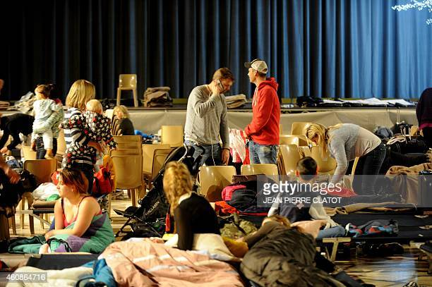 Holiday makers wake up after spending the night in a civic hall due to roads being blocked due to heavy snowfall in Albertville early on December 28...
