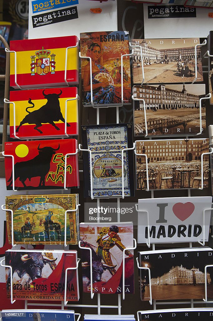 Holiday postcards stand for sale on a rack outside a souvenir store for tourists in Madrid, Spain, on Friday, June 8, 2012. Spain is poised to become the fourth of the 17 euro-area countries to require emergency assistance as the currency bloc's finance chiefs plan weekend talks on a potential aid request to shore up the nation's lenders. Photographer: Angel Navarrete/Bloomberg via Getty Images