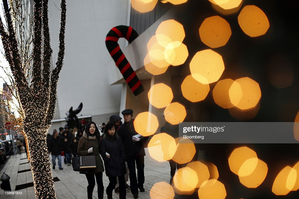 Holiday shoppers walk past a large candy cane Christmas decoration hanging from the side of the Solow Building in New York, U.S., on Sunday, Dec. 23, 2012. Holiday shoppers descended on U.S. stores this weekend in a last-minute dash to buy gifts amid concerns about the nation's economy and the impasse in Washington over taxes and spending. Photographer: Victor J. Blue/Bloomberg via Getty Images