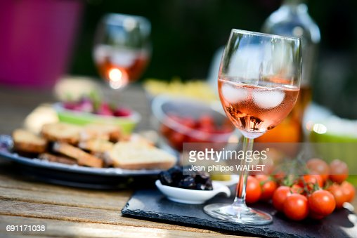 holiday summer brunch party table outdoor in a house backyard with appetizer, glass of rosé wine, fresh drink and organic vegetables : Foto de stock