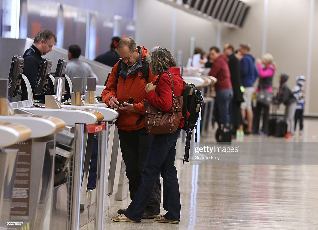 Holiday travelers check in at the Delta counter at the Salt Lake City international Airport on November 27, 2013 in Salt Lake City, Utah. A wintry storm system that is covering much of the nation is threatening to wreak havoc on holiday travel .