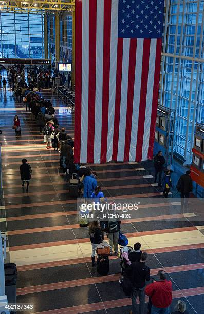 Holiday travelers line up for one of the TSA security checkpoints at Ronald Reagan National Airport in Washington on November 26 2013 as air traffic...