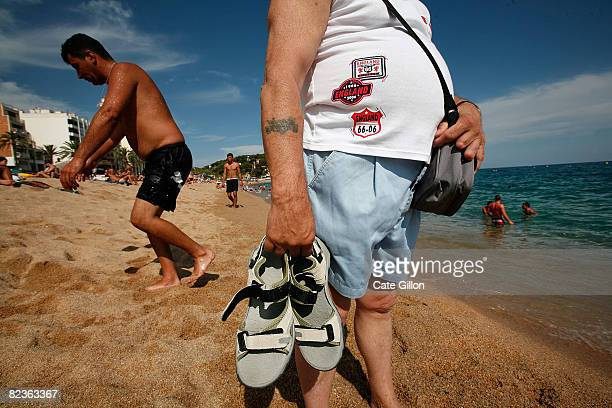 A holidaymaker from England stands watching the sea on the Platja de Lloret which this month is mainly visited by Italian and French tourists on...