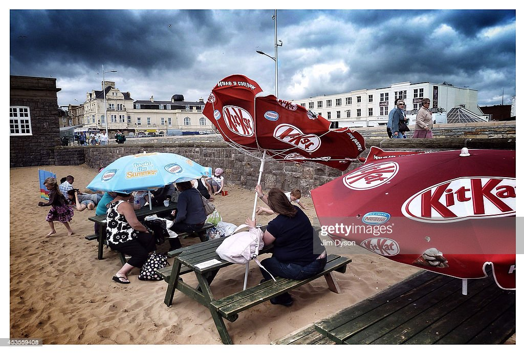 Holidaymakers brave the weather and shelter under an umbrella as another turns inside out in the wind, on the beach on July 29, 2010 in Weston-super-Mare, England.