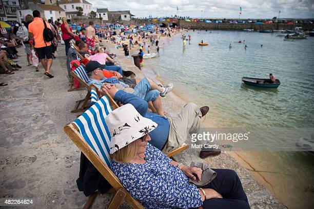 Holidaymakers enjoy the fine sunny weather as they gather around the harbour in St Ives on July 29 2015 in Cornwall England After a unsettled start...