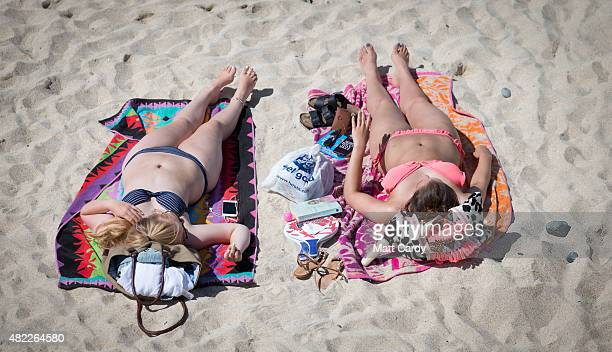 Holidaymakers enjoy the fine sunny weather at Porthmeor Beach in St Ives on July 29 2015 in Cornwall England After a unsettled start to the school...