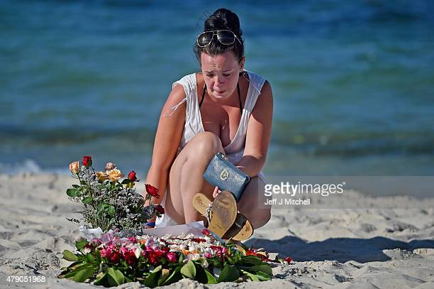 Holidaymakers lay flowers on Marhaba beach in Sousse where 38 people were killed in last Fridays terror attack on June 30 2015 in Sousse Tunisia...