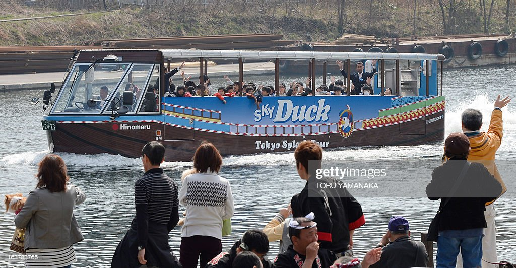 Holidaymakers look at the amphibious tourist bus 'Sky Duck' going into the water during the opening event of a tourist informantion center in the riverside on March 16, 2013. Japan's Hinomaru bus service company will begin a sightseeing service with two amphibious buses from March 17 for the first time in Tokyo. AFP PHOTO/Toru YAMANAKA