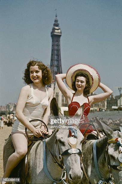 Holidaymakers riding donkeys on the beach at Blackpool Lancashire July 1954 Blackpool Tower is in the background Original publication Picture Post...