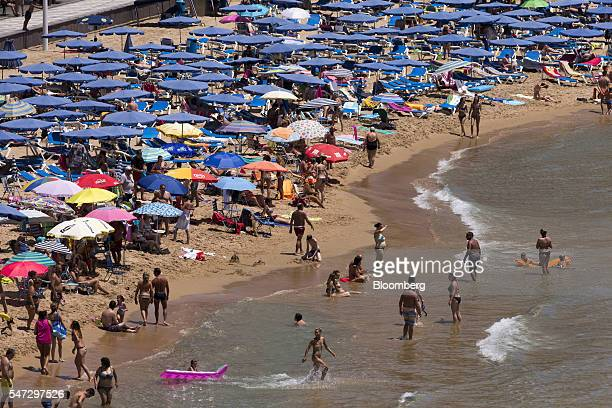 Holidaymakers sit beneath parasols and play in the surf on the beachfront in Benidorm Spain on Tuesday July 12 2016 Spain registered record tourism...