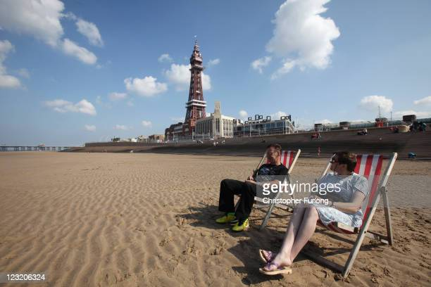 Holidaymakers sit on the beach next to the refurbished Blackpool Tower on September 1 2011 in Blackpool England After a 20million GBP refurbishment...
