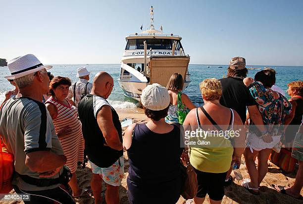 Holidaymakers wait to board a tour boat on Fenals beach on August 18 2008 in Lloret de Mar Spain Feeling the pinch from the credit crunch many...