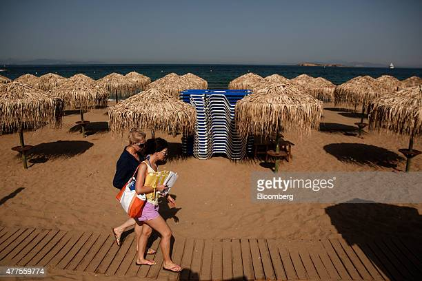 Holidaymakers walk along a wooden path past a stack of sunloungers on the beach in Kavouri Greece on Monday June 15 2015 The tourism industry...