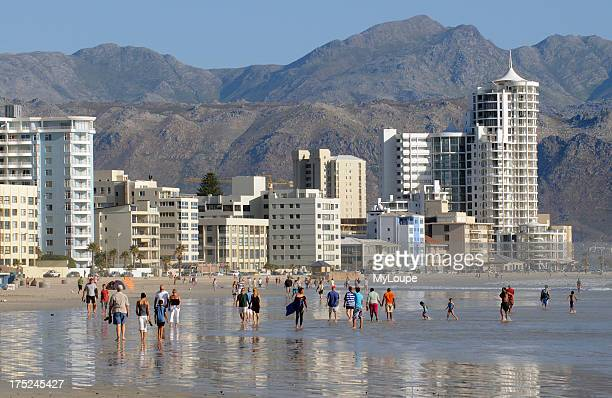 Holidaymakers walking on the beach in the western cape seaside resort of Strand close to Somerset West South Africa