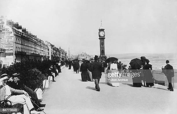Holidaymakers walking past Queen Victoria's Jubilee Clock on the esplanade at Weymouth Dorset circa 1890