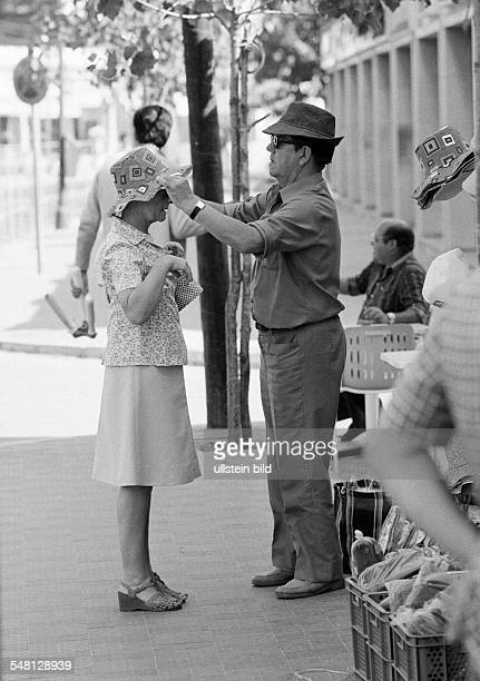 holidays tourism souvenir shop older couple trying on of a hat man puts on a sun bonnet to his woman aged 60 to 70 years Spain Balearic Islands...