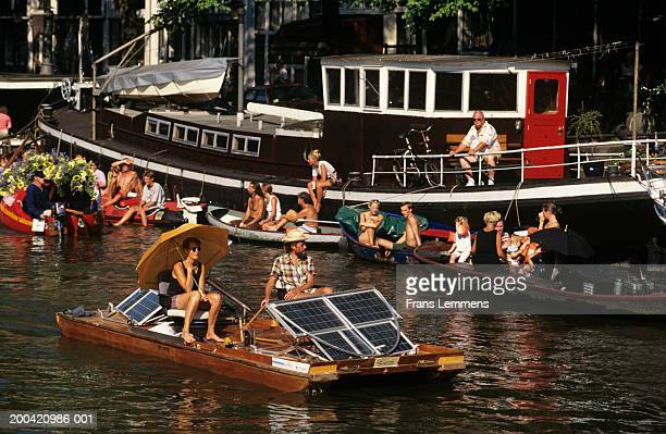 Holland, Amsterdam, couple on solar powered boat on canal