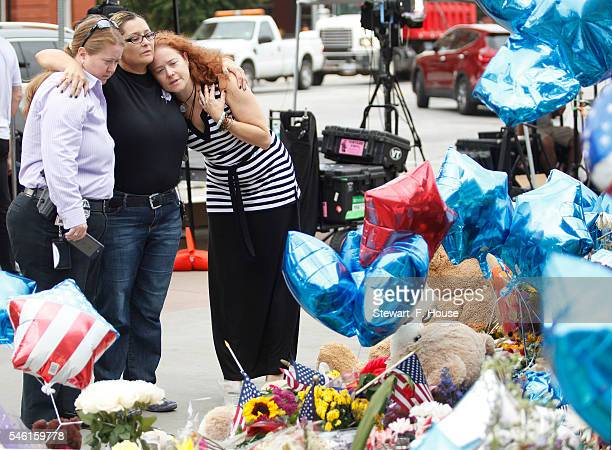 Holland Barton Elaine Hassmann and Michelle Weisskopf all members of the Dallas Police Department look over items left by the public in memorial at...