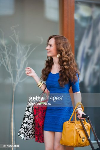 Holland, Goirle, elegant woman carrying trolley and shopping bags : Stock Photo
