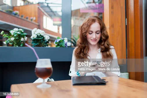 Holland, Goirle, elegant woman in cafe using mobile phone : Stock Photo