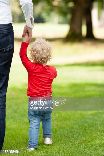 Holland, Tilburg, rear view of girl (2-3) walking with her mother : Stock Photo