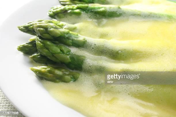 Hollandaise sauce over asparagus in a white dish