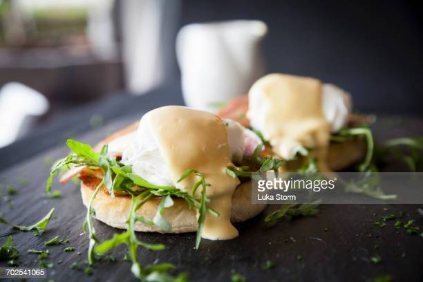 Hollandaise sauce over eggs benedict breakfast on slate