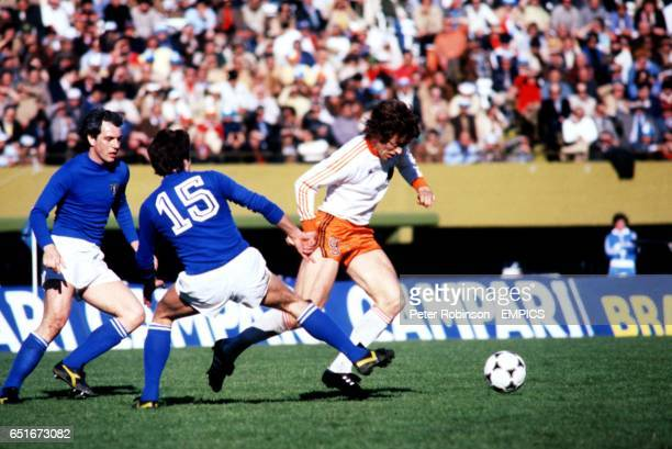 Holland's Arie Haan skips past Italy's Roberto Bettega and Gaetano Scirea