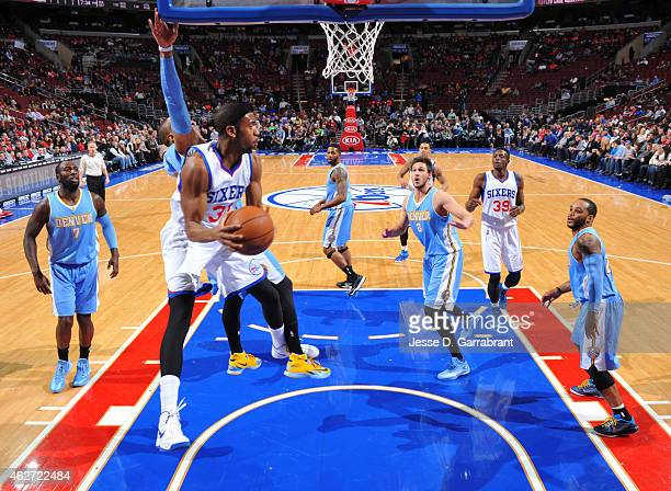 Hollis Thompson of the Philadelphia 76ers looks to pass the ball in midair against the Denver Nuggets at Wells Fargo Center on February 3 2015 in...