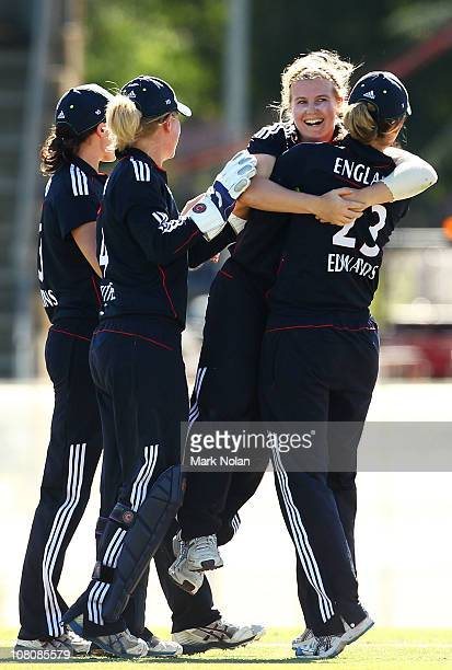Holly Colvin of England celebrates a wicket with team mates during the fourth Twenty20 match between Australia and England at Manuka Oval on January...