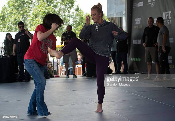 Holly Holm of the United States brings a fan on stage during an open workout for fans and media at Federation Square on November 12 2015 in Melbourne...