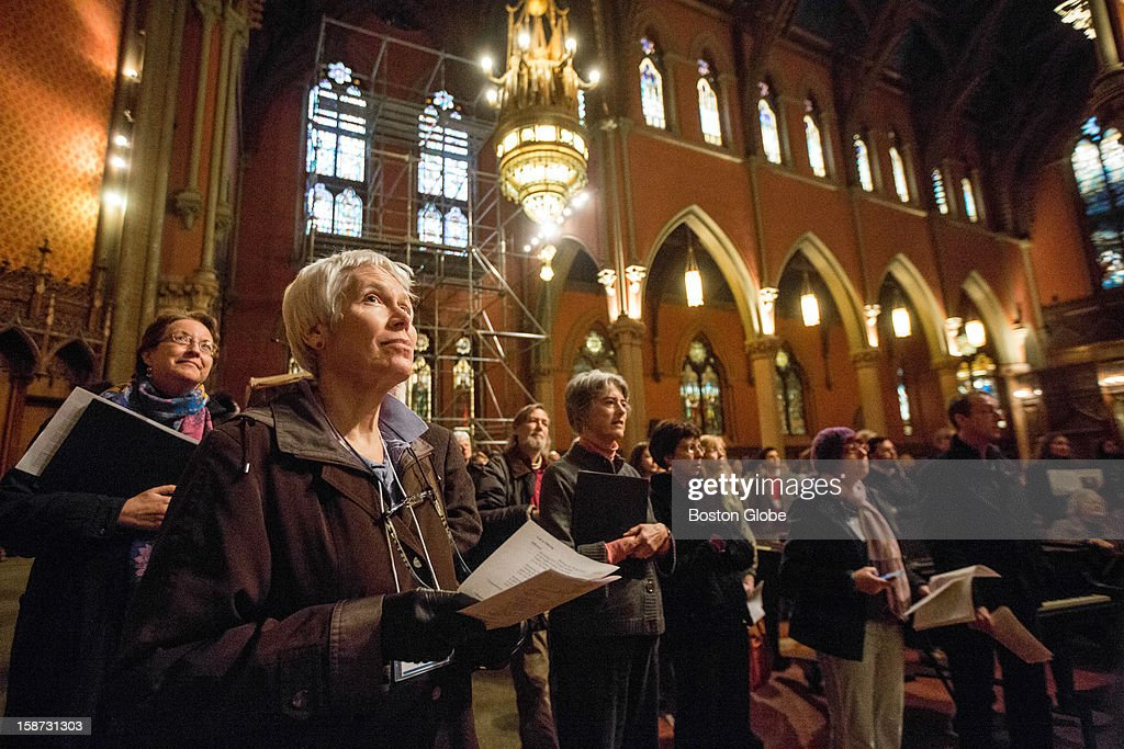 Holly Humphreys, front left, and fellow congregation members looked up at the window during the rededication of the 'Dorcas Window' at the Church of the Covenant on Newbury Street in Boston. Part of the stained glass window was shattered during a break-in last year.