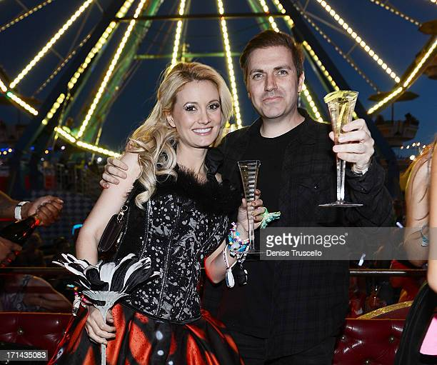 Holly Madison and Pasquale Rotella pose for photos in front of the Ferris wheel where he asked for her hand in marriage during the 17th annual...