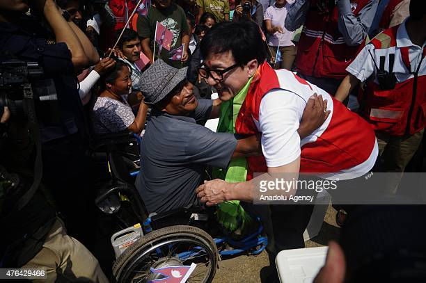 Hollywood actor Jackei Chan embraces a man on wheelchair during relief distribution to the earthquake victims in Lalitpur on June 9 2015 Jackie Chan...