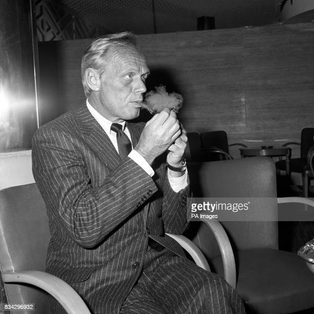 Hollywood actor Richard Widmark relaxing over a pipe of tobaccoat a press reception at the Savoy Hotel Richard was in Europe as part of an extensive...