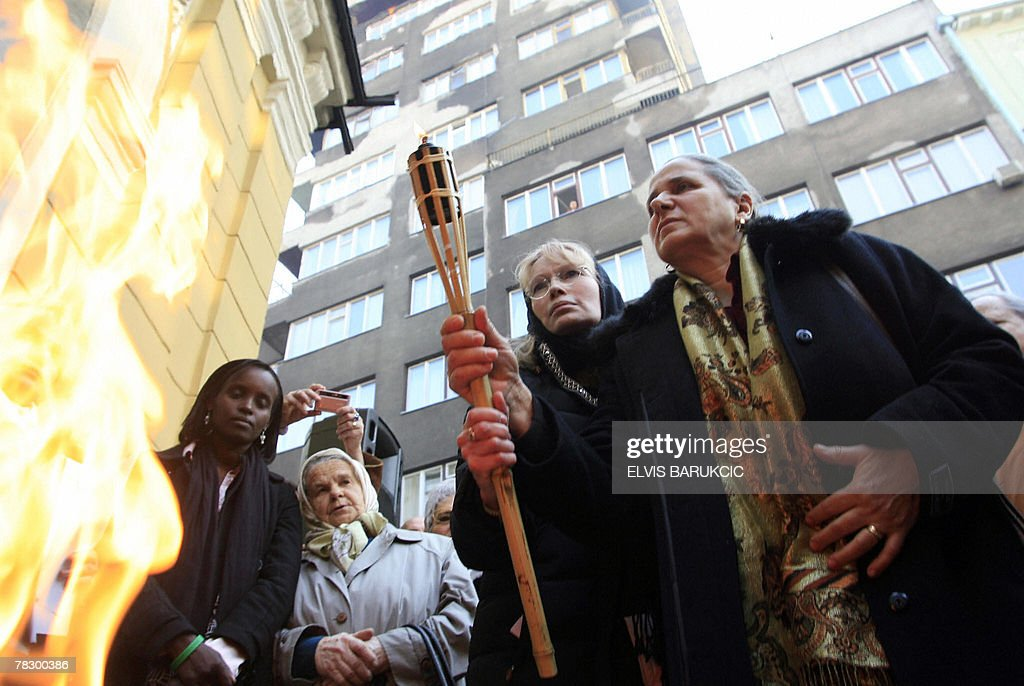 Hollywood actress and UNICEF ambassador Mia Farrow (L) and Srebrenica genocide survivor, Hatidza Mehmedovic (R) light an Olympic-style torch together with survivors of Bosnia's genocide in Sarajevo, Bosnia on 07 December, 2007. Mia Farrow is part of a campaign that calls on China to press Sudan to end abuses in its Darfur region. The Dream for Darfur Olympic torch was first time lit last August at the Darfur-Chad border and has so far toured Rwanda, Armenia and Germany. It is planned to pass Cambodia before reaching China in early 2008. AFP PHOTO ELVIS BARUKCIC