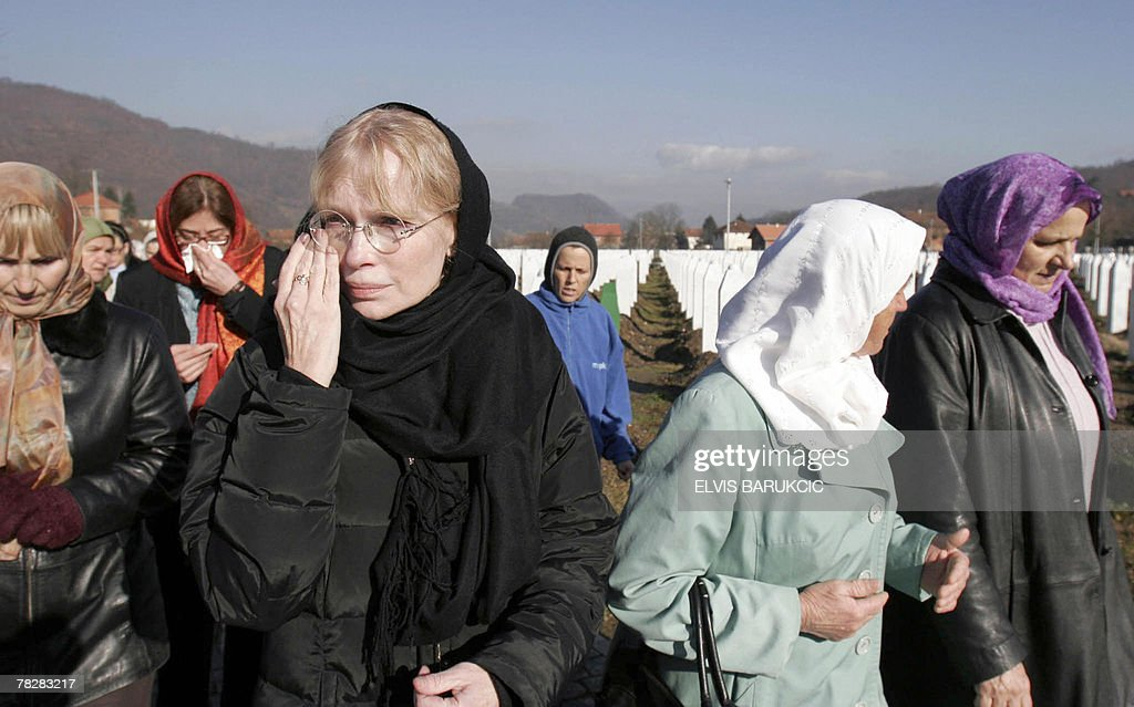 Hollywood actress and UNICEF ambassador Mia Farrow (C) wipes a tear as she visits the cemetery where up to 8,000 Muslim victims of the 1995 massacre are buried, in Srebrenica, 06 December 2007. Farrow and fellow activists begun an Olympic-style torch relay through countries that have suffered genocide to press China to help end abuse in its ally Sudan's Darfur region. AFP PHOTO / ELVIS BARUKCIC