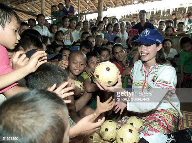 Hollywood actress Angelina Jolie distributes balls to the children at the Tham Hin refugee camp on the ThaiBurma border 19 May 2002 Jolie visited the...