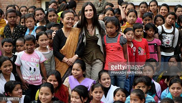 Hollywood actress Demi Moore and Maiti Nepal Chairperson Anuradha Koirala stand with children at a rehabilitation centre for victims of human...