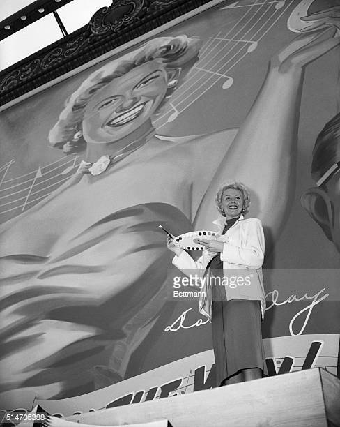 3/8/1954 Hollywood CA A personal touch Screen star Doris Day gives out with a big smiles after autographing a giant portrait of herself The 35foot...
