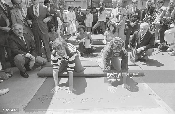 George Lucas and Steven Spielberg the two men responsible for the six most popular films of all time place their hands and feet in cement in the...