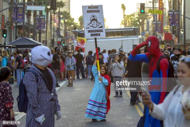 Hollywood character impersonators walk near a girl carrying a sign on Hollywood Boulevard during an event celebrating Indigenous Peoples Day in the...