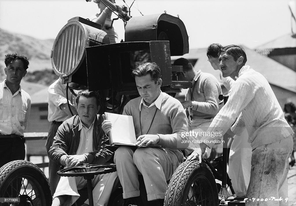 Hollywood director Lewis Milestone (1895 - 1980) consults his notes on the set of 'Rain', an early talkie starring Joan Crawford.