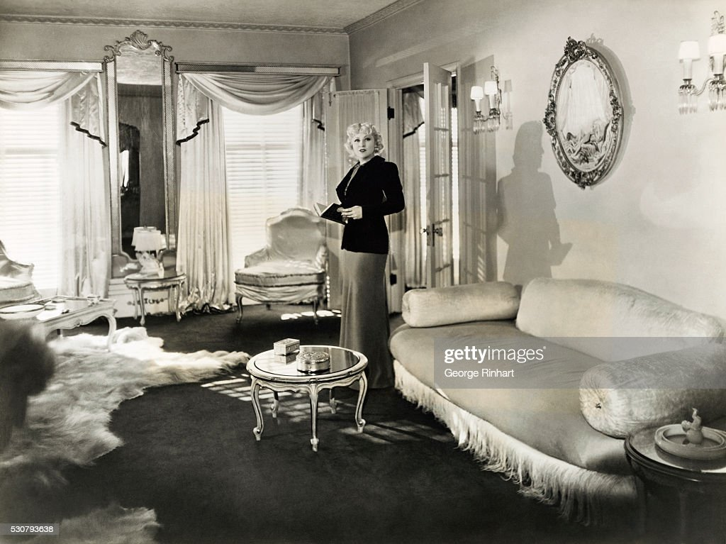 Mae West, Paramount star, invites the cameraman to 'come up and see her' in her Hollywood home. Most of the rooms are in Louis XIV style and in shades of white and gold.
